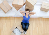 Beautiful woman sitting between boxes at home — Stock Photo