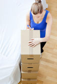 Caucasian woman is moving various boxes — Stock Photo