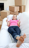 Attractive woman relaxing on a sofa with boxes — Stock Photo