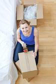 Smiling woman closing a box — Stock Photo