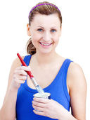 Attractive woman using a paintbrush — Stock Photo