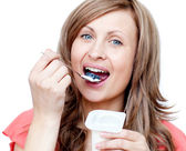 Lively woman eating a yogurt — Stock Photo
