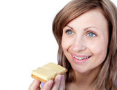 Cheerful woman eating a cracker with cheese — Stock Photo