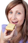 Charming woman eating a cracker with cheese — Stock Photo