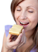 Young woman eating a cracker with cheese — Stock Photo