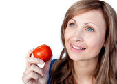 Positive woman holding a tomato — Stock Photo