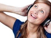 Delighted woman listening music with headphone — Stock Photo