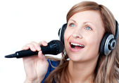 Delighted woman listening music with headphone and singing — Stock Photo
