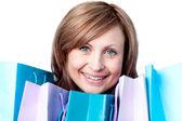 Uśmiechnięta kobieta pokazano jej torby na zakupy — Zdjęcie stockowe