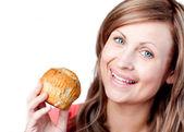 Mulher sorridente é comer um muffin — Foto Stock