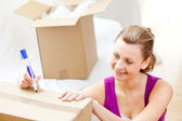 Happy woman writing on boxes using a pen — Stock Photo