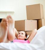 Cute woman having a break between boxes — Stock Photo