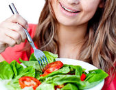 Close-up of a delighted woman is eating a salad — Stock Photo
