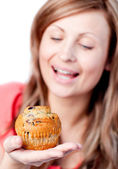 Radiant woman is eating a muffin — Stock Photo