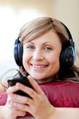 Delighted woman is listening the music in the living-room — Stock Photo