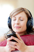 Radiant woman is listening the music in the living-room — Stock Photo