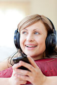 Caucasian woman is listening the music in the living-room — Stock Photo