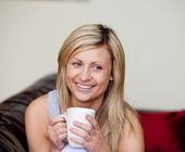 ソファの上にコーヒーを一杯飲み白人女性 — ストック写真