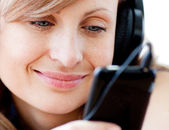 Portrait of a delighted woman listening the music with headphone — Stock Photo