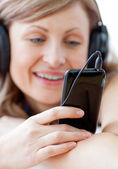 Portrait of a happy woman listening the music with headphones — Stock Photo