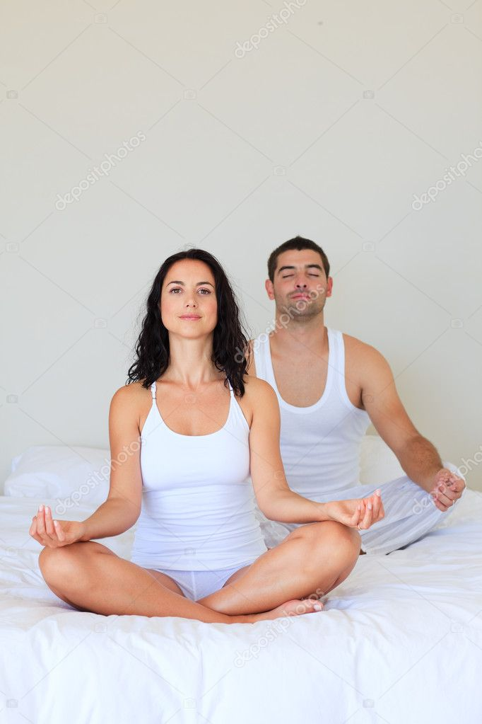 Young couple in meditation pose on bed — Stockfoto #10311573