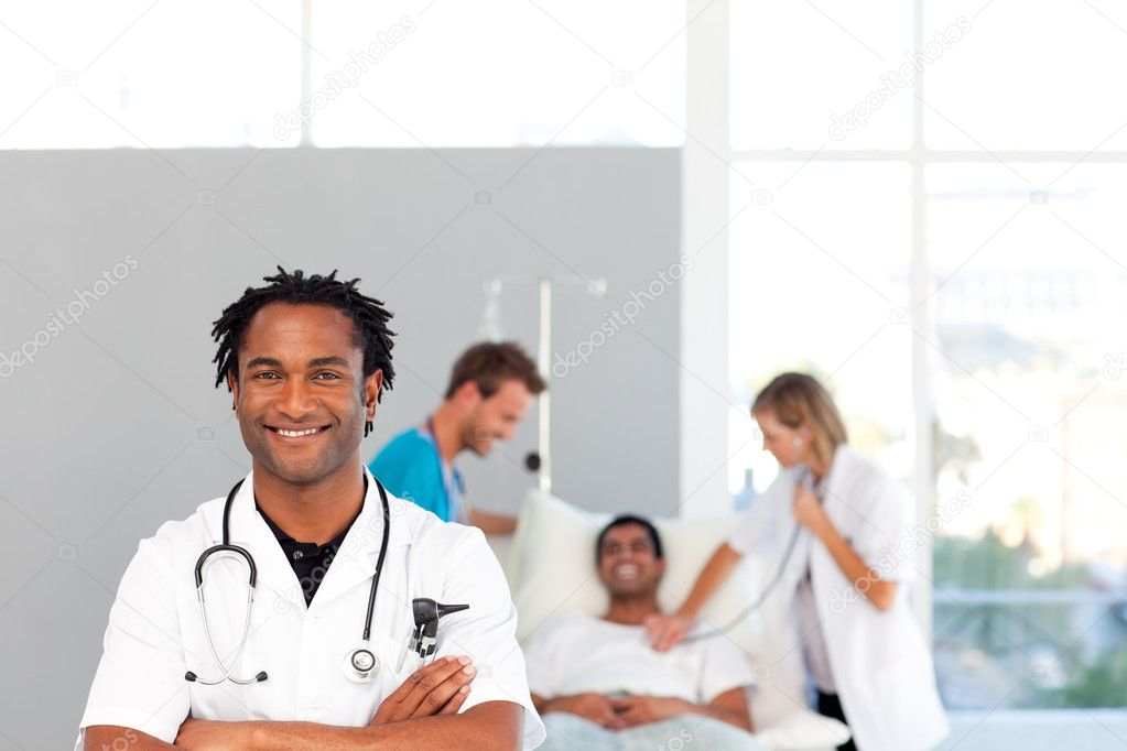 Smiling African doctor with his colleagues in the background — Stock Photo #10313232
