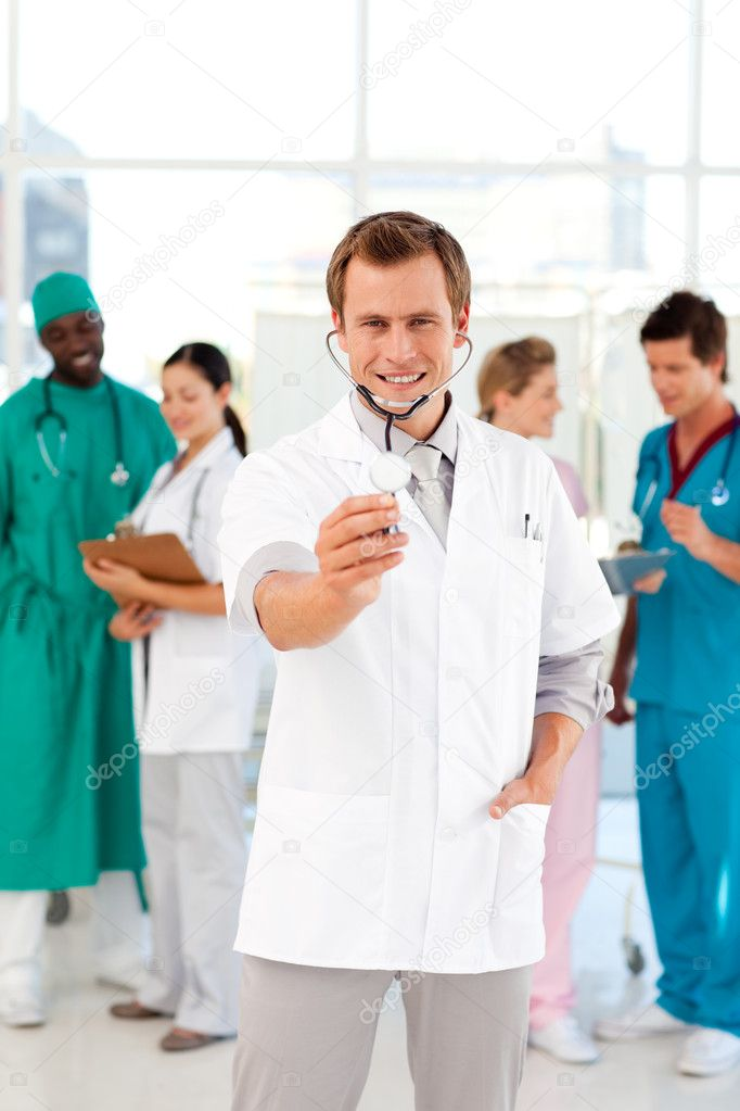 Doctor with stethoscope and his team in the background — Stock Photo #10313451