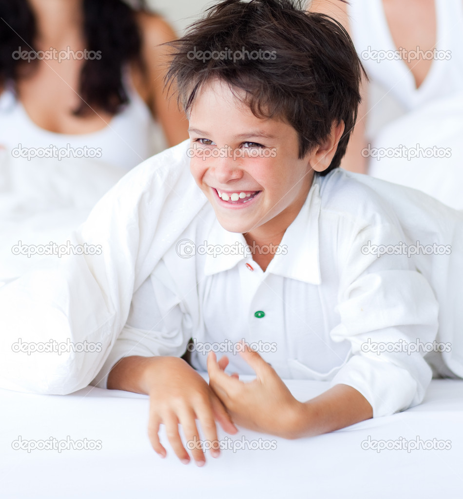 Portrait of a smiling son having fun with his parents in bed — Stock Photo #10313979