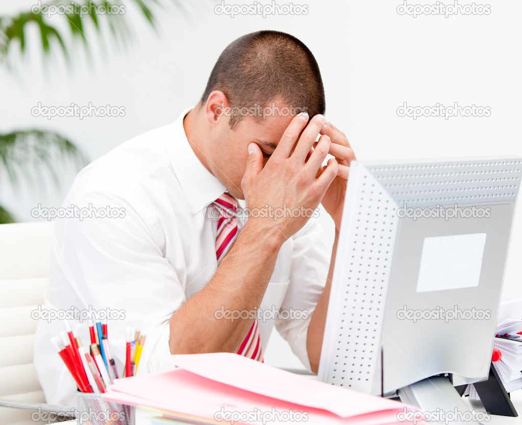 Frustrated businessman working at a computer in the office  Stock Photo #10315903