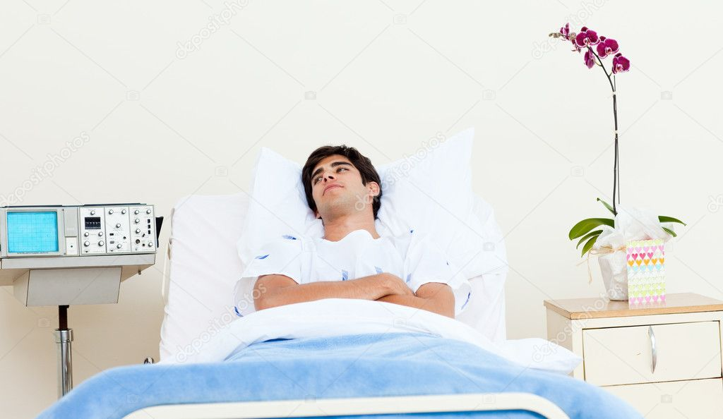 male patient lying on a hospital bed � stock photo