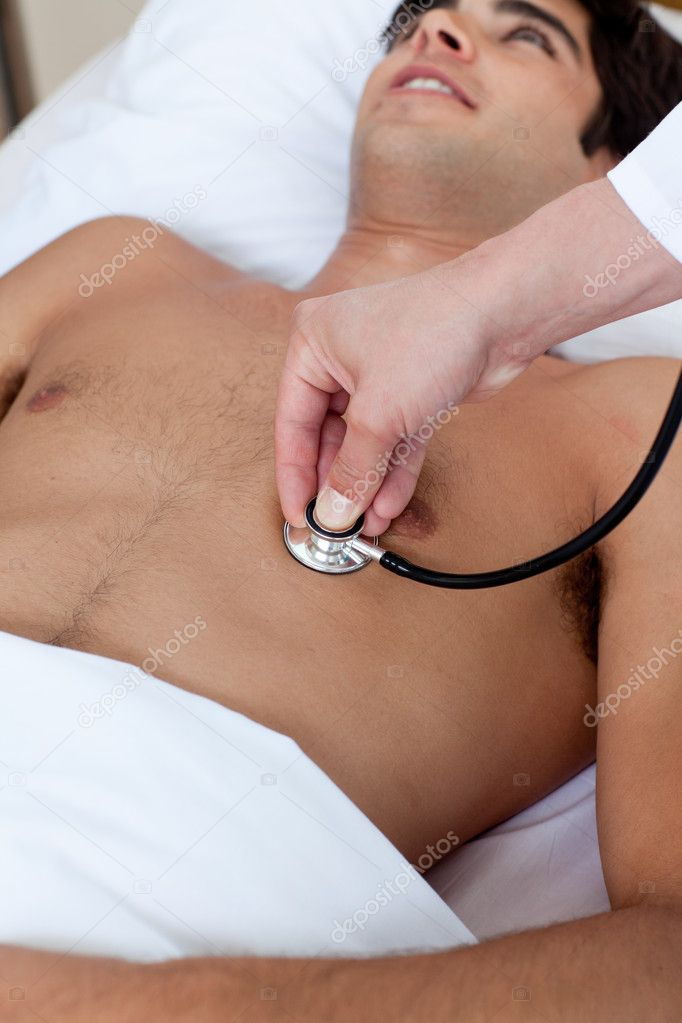 A doctor checking the pulse of a patient lying on a hospital bed — Stock Photo #10317226