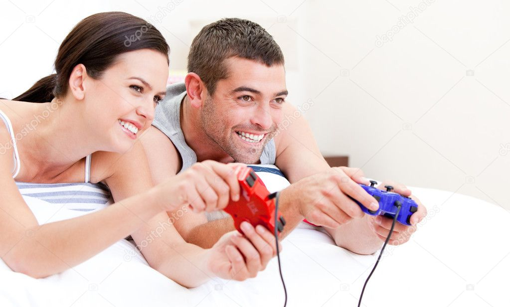United couple playing video games against a white background — Stock Photo #10317597