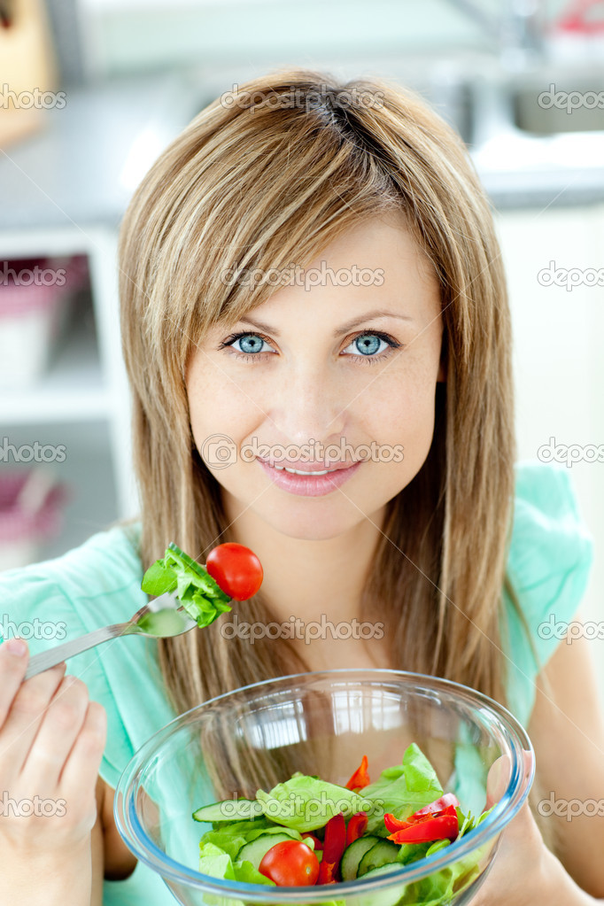 Radiant woman eating a salad in the kitchen at home  Stock Photo #10318529