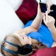 Delighted woman is listening the music with headphones — ストック写真