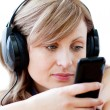 Charming woman is listening the music with headphones — Stock Photo