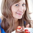 Cheerful woman holding a piece of chocolate cake — ストック写真