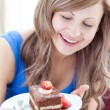 Happy woman holding a piece of chocolate cake — Stock Photo