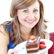 Smiling woman holding a piece of chocolate cake — Stok fotoğraf