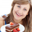 Bright woman holding a piece of chocolate cake — Stok fotoğraf