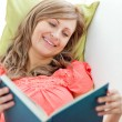 Smiling woman reading a book lying on a sofa - Stok fotoğraf