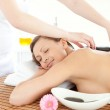 Portrait of a relaxed woman having a massage with stones — Stock Photo