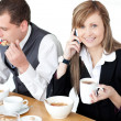 Stock Photo: Smiling businesswomtalking on phone while having breakfast wi