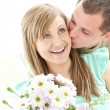 Stock Photo: Attentive man giving a bunch of flowers to his girlfriend