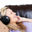 Smiling woman using headphones — Stock Photo