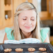 Foto Stock: Delighted housewife preparing cookies