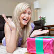 Astonished woman looking at a present — Stock Photo #10320679