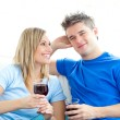 Cute couple drinking wine together in the living-room - Stock Photo