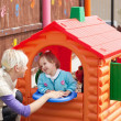 Sweet girl standing in a small house at the playground - Photo