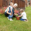 Smiling woman with two children in the garden — Stock Photo