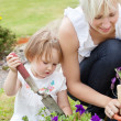 Little girl with purple flowers — Stock Photo